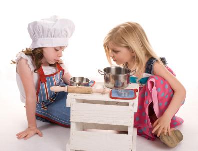 Två flickor leker i leksakskök